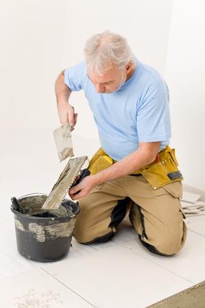 Home improvement, renovation - handyman laying tile, trowel with mortar Stock Photo - 8569207