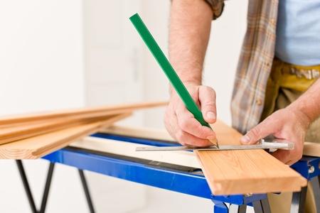 Home improvement - close-up of handyman measure wooden floor Stock Photo - 8569192