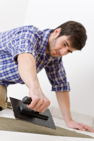 Home improvement, renovation - handyman laying tile, trowel with mortar photo