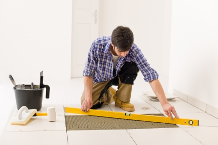 tile floor: Home tile improvement - handyman with level laying down tile floor