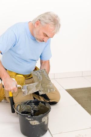 Home improvement, renovation - handyman laying tile, trowel with mortar Stock Photo - 8569246