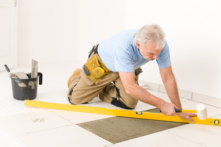 lying on floor: Home improvement, renovation - handyman laying ceramic tile with level Stock Photo