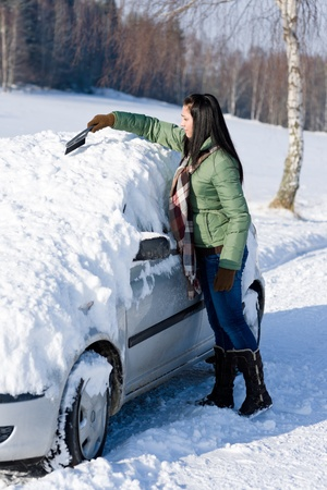 remove: Winter car - woman remove snow from windshield with snow brush