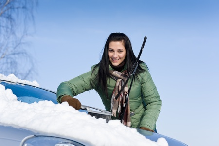 Winter car - woman remove snow from windshield with snow brush photo