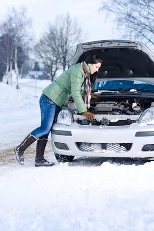 try: Winter car breakdown - woman try to repair motor Stock Photo