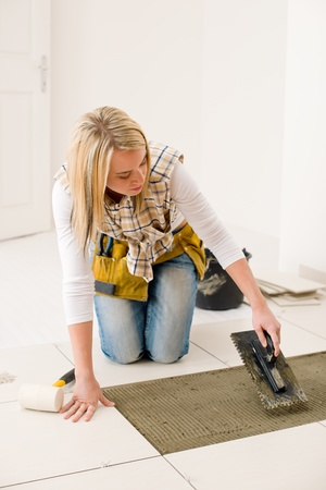 Home improvement, renovation - handywoman laying tile, trowel with mortar Stock Photo - 8605688