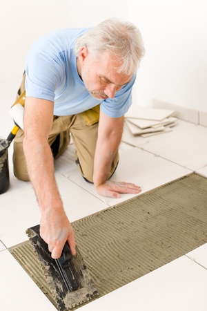 Home improvement, renovation - handyman laying tile, trowel with mortar Stock Photo - 8605701