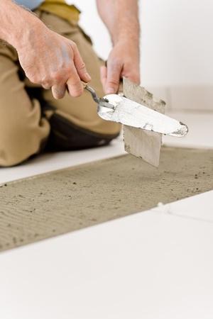 Home improvement, renovation - handyman laying tile, trowel with mortar Stock Photo - 8605682