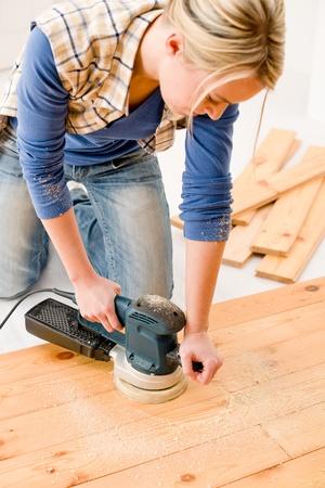 new construction renovation: Home improvement - handywoman sanding wooden floor in workshop