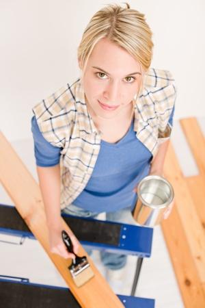 Home improvement - handywoman painting wooden plank in workshop photo
