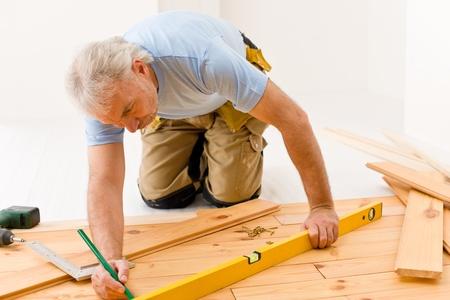 floor level: Home improvement - handyman installing wooden floor home Stock Photo