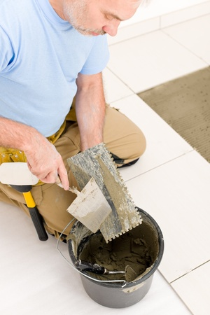 Home improvement, renovation - handyman laying tile, trowel with mortar Stock Photo - 8641954