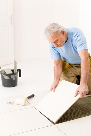 Home improvement, renovation - handyman laying ceramic tile Stock Photo - 8641939