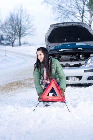 winter woman: Winter car breakdown - woman placing warning triangle Stock Photo