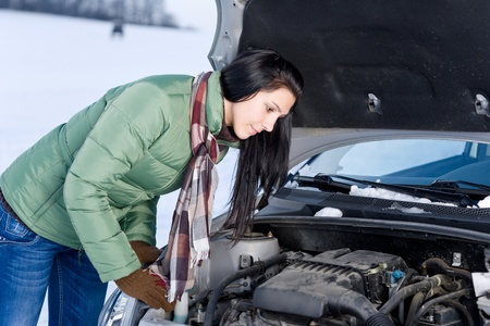 Winter car breakdown - woman try to repair motor photo
