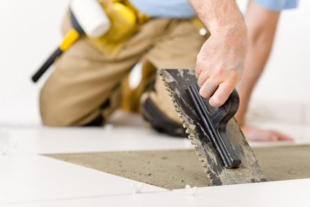 home improvement: Home improvement, renovation - handyman laying tile, trowel with mortar