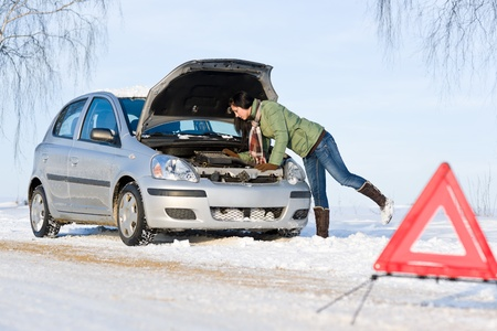 troubles: Winter car breakdown - woman try to repair motor Stock Photo