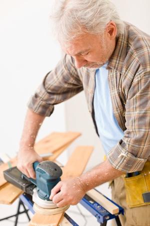 Home improvement - handyman sanding wooden floor in workshop Stock Photo - 8641981