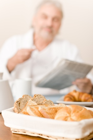 Senior mature man - breakfast pastry and bread in wicker basket photo