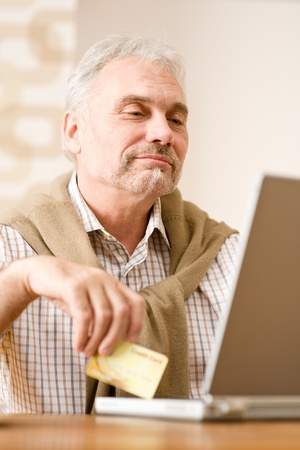 Senior mature man - home shopping with credit card and laptop photo