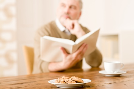 Senior mature man reading book, cookies at wooden table photo