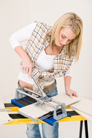 Home improvement - handywoman cutting tile with jigsaw photo