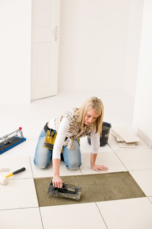 Home improvement, renovation - handywoman laying tile, trowel with mortar photo