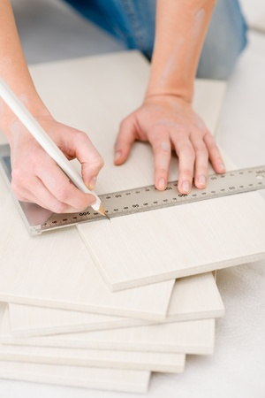 Home improvement - handywoman measuring tile, focus on ruler photo