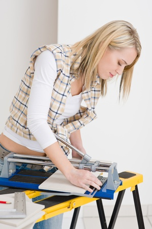Home improvement - handywoman cutting tile with jigsaw photo