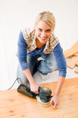Home improvement - handywoman sanding wooden floor in workshop photo