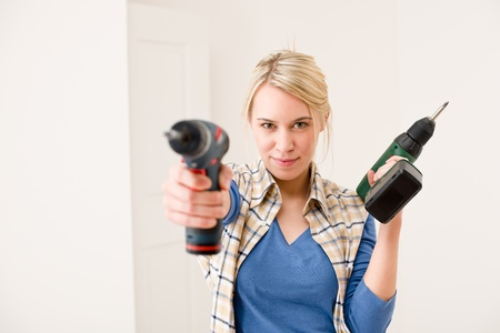 renovation: Home improvement - woman with battery cordless screwdriver Stock Photo