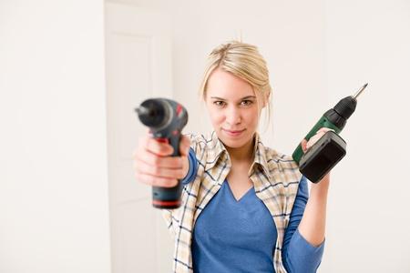 Verbetering van het huis - vrouw met batterij cordless schroeven draaier Stockfoto