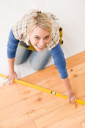 Home improvement - handywoman installing wooden floor home photo