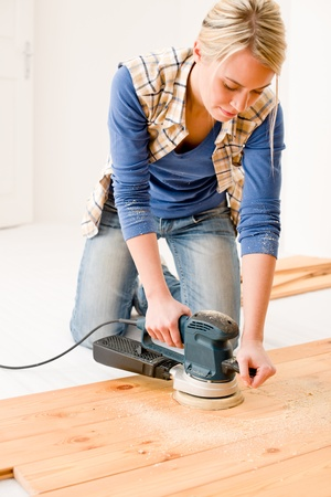 Home improvement - handywoman sanding wooden floor in workshop photo