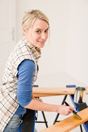Home improvement - handywoman painting wooden plank in workshop Stock Photo - 8744794