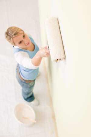 Home improvement - handywoman painting wall with roller photo