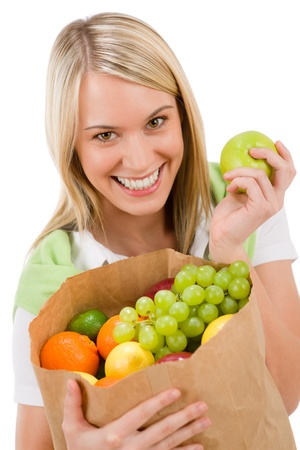 Healthy lifestyle - cheerful woman with fruit shopping paper bag on white background photo