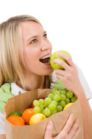 Healthy lifestyle - woman with fruit shopping paper bag bite apple on white background photo