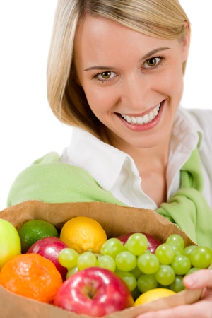 Healthy lifestyle - woman with fruit shopping paper bag on white background photo