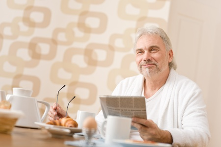 Senior mature man - breakfast at home with newspaper at desk photo