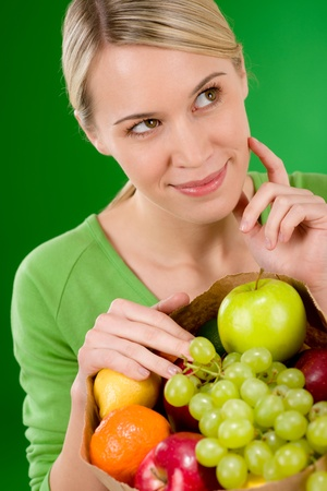 Healthy lifestyle - thoughtful woman with fruit shopping paper bag on green background photo