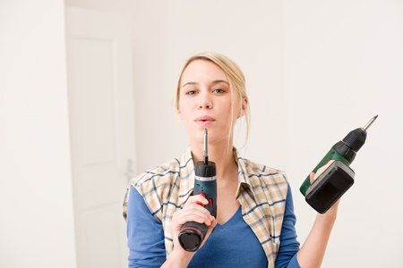 Home improvement - woman with battery cordless screwdriver photo
