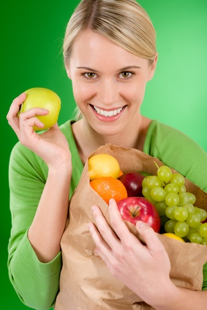apple paper bag: Healthy lifestyle - woman with fruit shopping paper bag on green background