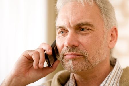 Thoughtful senior mature man call, holding mobile phone photo