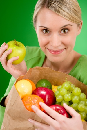 Healthy lifestyle - woman with fruit shopping paper bag on green background photo
