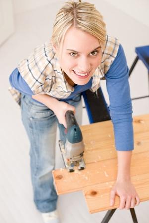 Home improvement - handywoman cutting wooden floor  with jigsaw photo