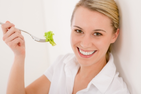Healthy lifestyle - woman eat slice of orange, fruit salad