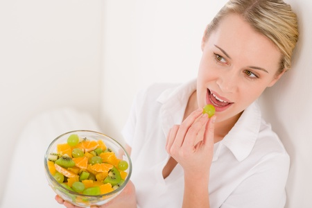 Healthy lifestyle - woman eat slice of orange, fruit salad Stock Photo - 8744986