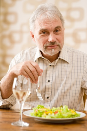 Senior mature man eat vegetable salad and white wine at wooden table photo