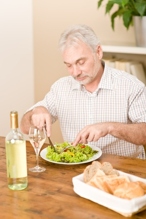 Senior mature man eat vegetable salad and white wine at wooden table, focus on salad photo